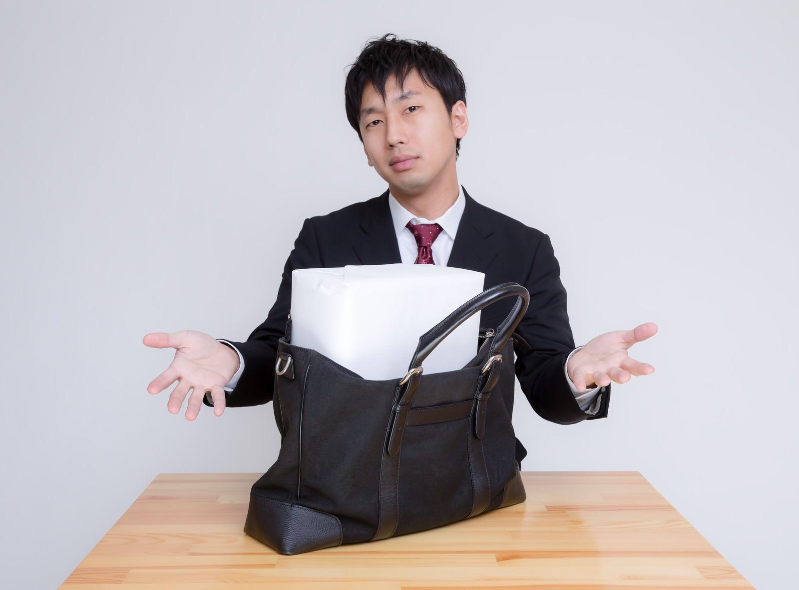 札束に見立てた箱がかばんに入らない男性 のフリー素材