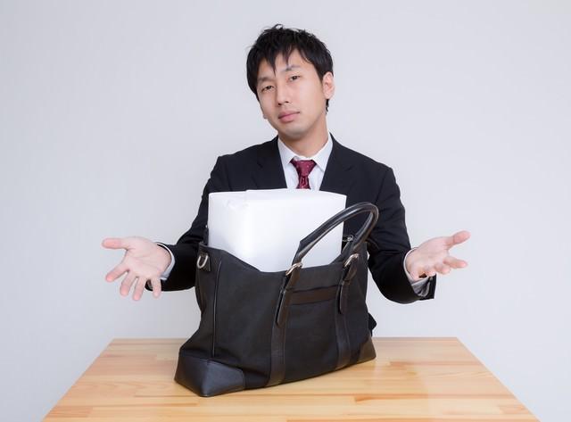 札束に見立てた箱がかばんに入らない男性 の写真