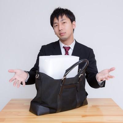 「札束に見立てた箱がかばんに入らない男性 」の写真素材