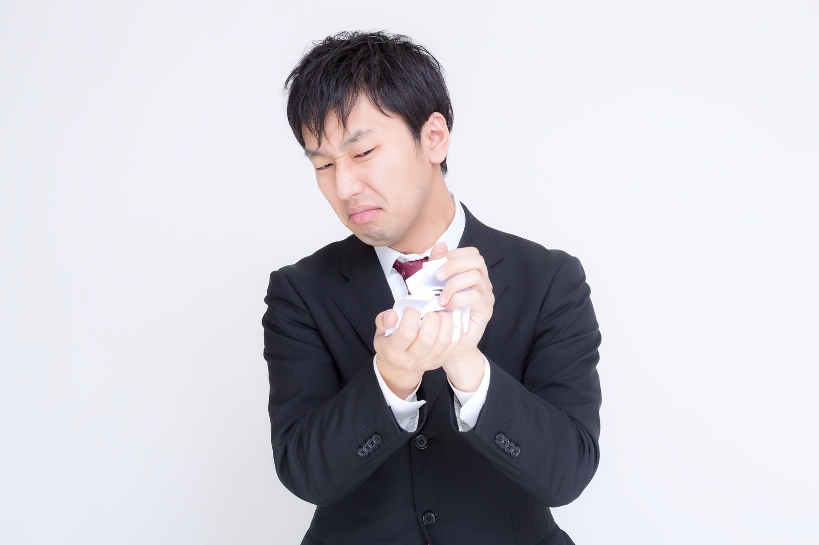「紙屑を丸めるサラリーマン」の写真[モデル:大川竜弥]