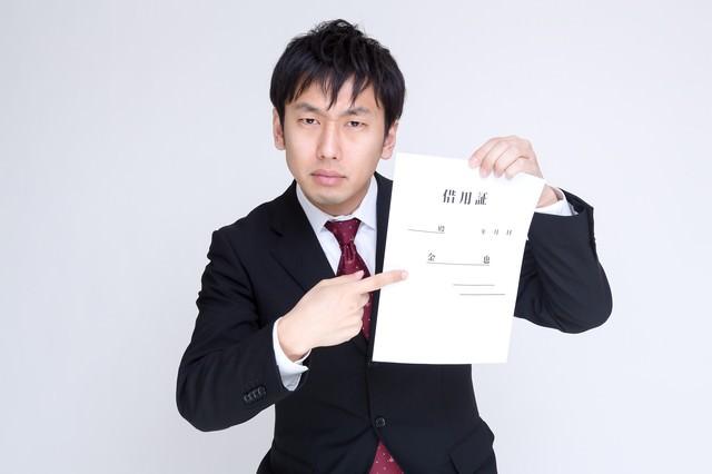 怖い顔で借用証について言及する男性の写真