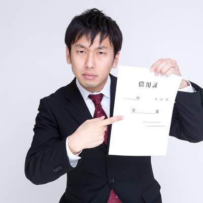 「怖い顔で借用証について言及する男性」の写真素材