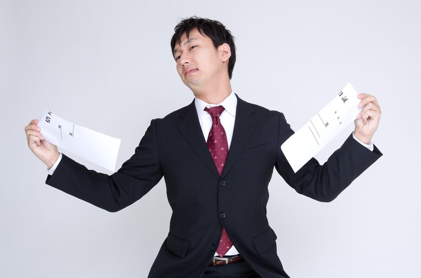 「簡素な借用証を力いっぱい引き裂くスーツ姿の男性」の写真[モデル:大川竜弥]