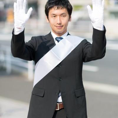 「両手をあげて支援を呼びかける党公認候補」の写真素材