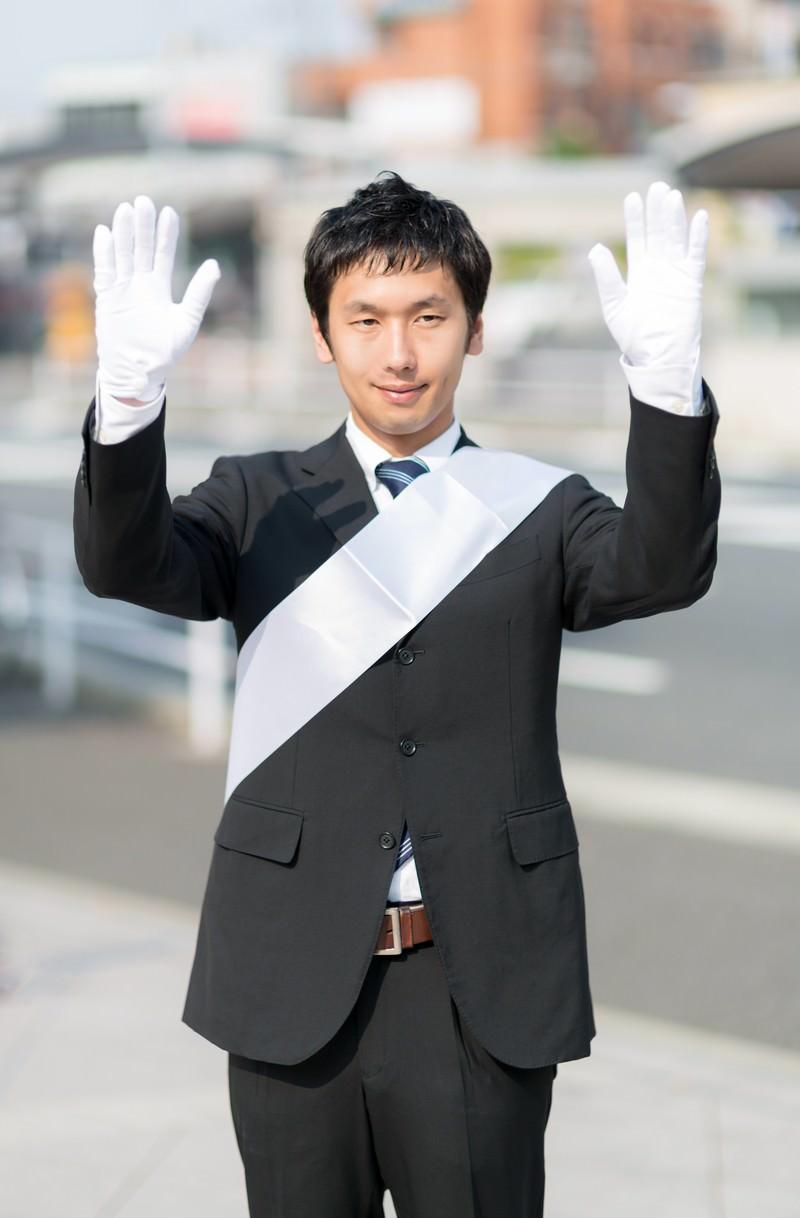 「両手をあげて支援を呼びかける党公認候補」の写真[モデル:大川竜弥]