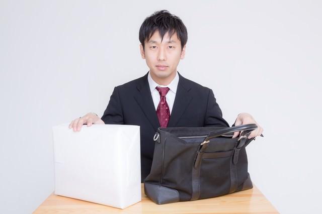 借用した現金とそれを運んだかばんを用意する男性の写真
