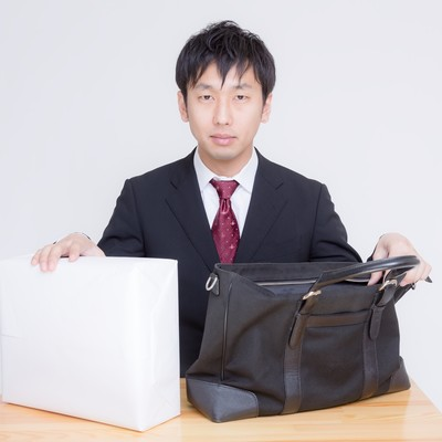 「借用した現金とそれを運んだかばんを用意する男性」の写真素材