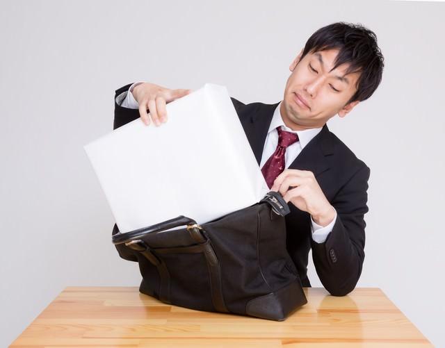 札束に見立てた白い箱をかばんに押し込む男性の写真