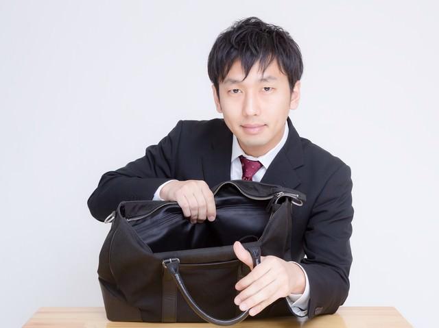 かばんの中身を見せるサラリーマンの写真