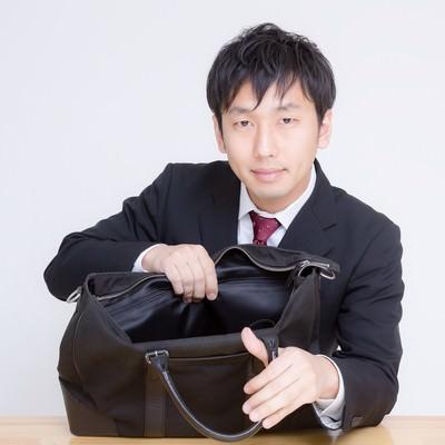「かばんの中身を見せるサラリーマン」の写真素材