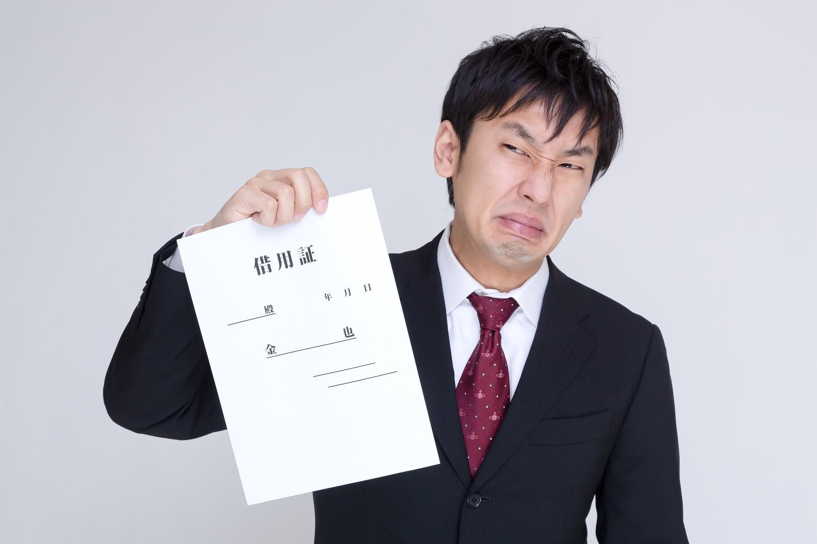 「簡素な借用証を提示して墓穴を掘る男性」の写真[モデル:大川竜弥]