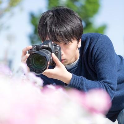 「一眼レフで花を接写するカメラマン」の写真素材