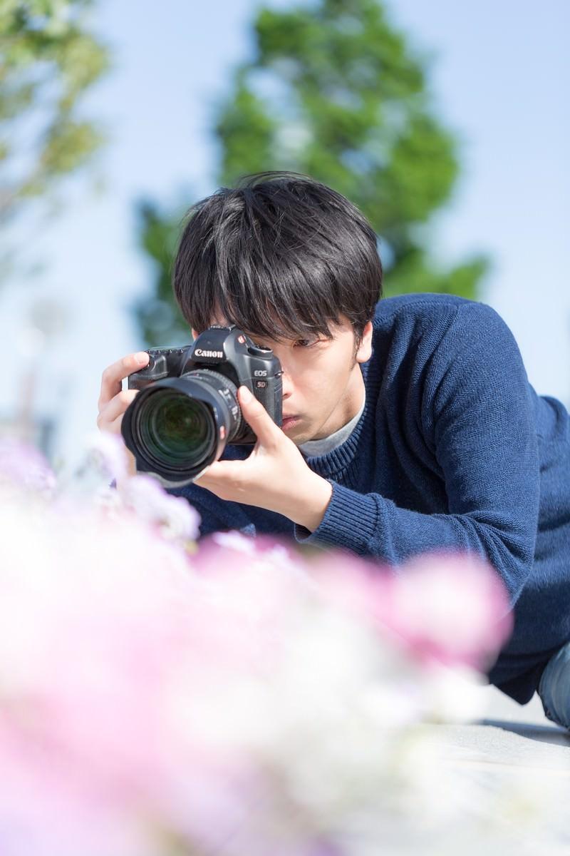 「一眼レフで花を接写するカメラマン」の写真[モデル:大川竜弥]