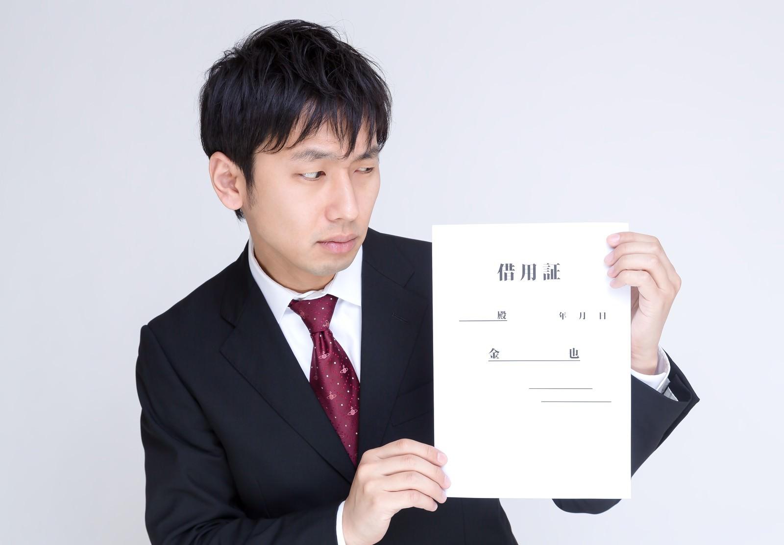 「借用証を怪しむ男性」の写真[モデル:大川竜弥]
