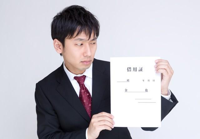 借用証を怪しむ男性の写真
