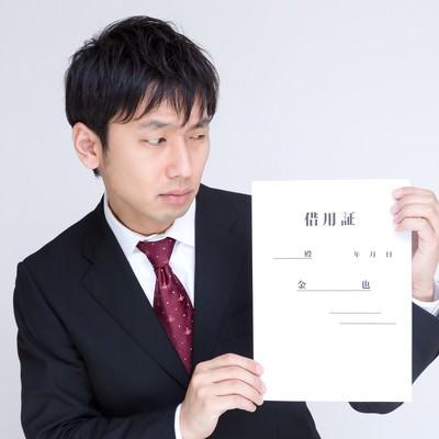 「借用証を怪しむ男性」の写真素材