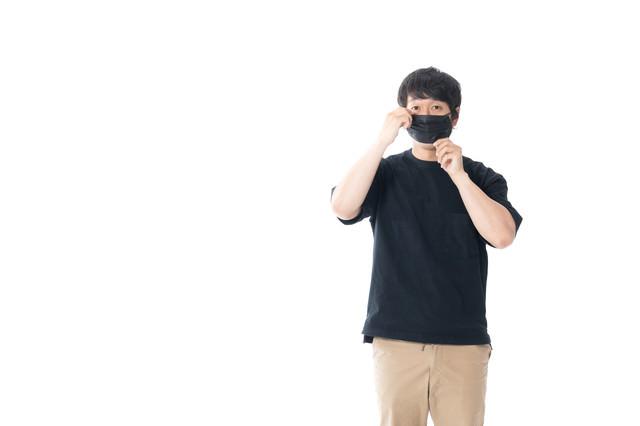 批判されても黒マスクを着ける男性の写真