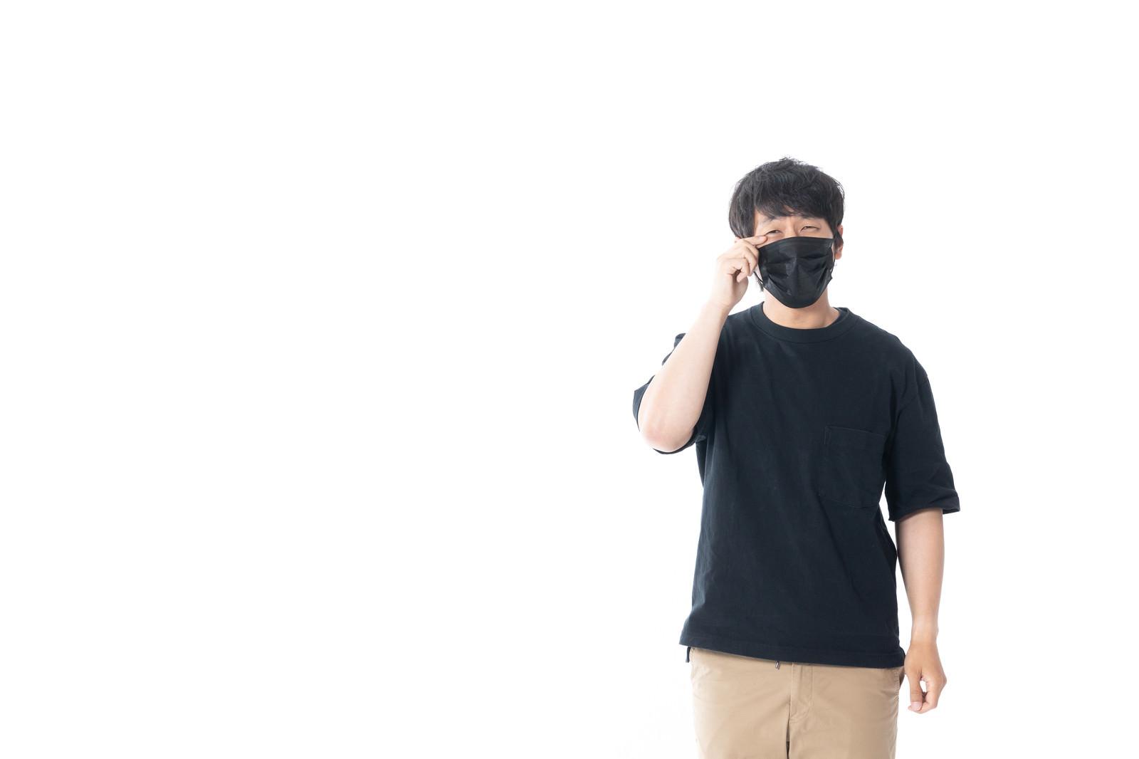 「花粉症でマスクをしても目が痒い男性」の写真[モデル:大川竜弥]