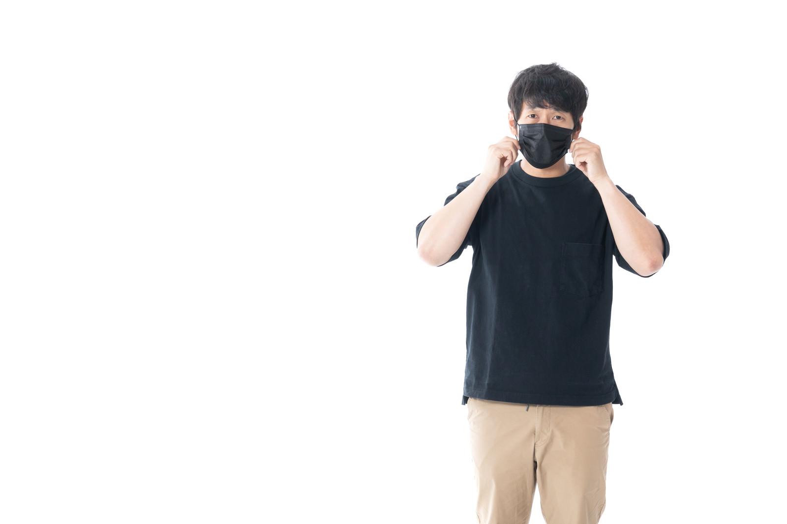 「黒いマスクで顔を覆う男性」の写真[モデル:大川竜弥]