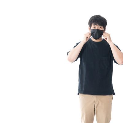 黒いマスクで顔を覆う男性の写真