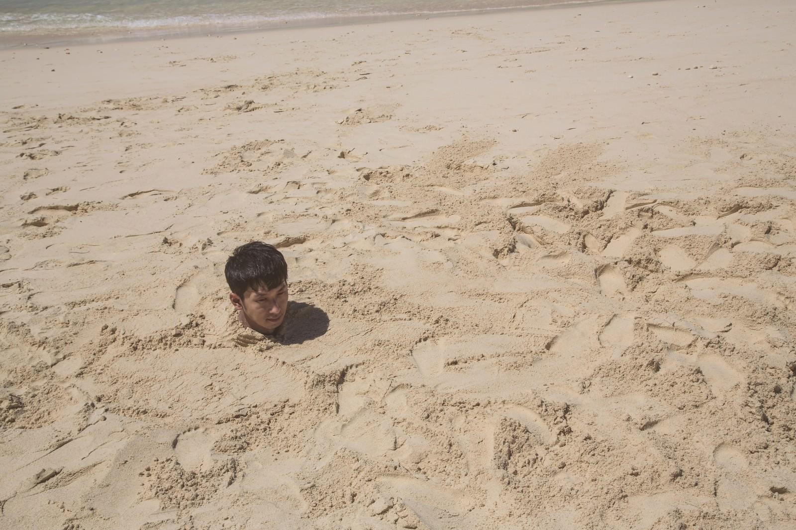 「砂浜に埋まり自身の影で方角を確認する男性」の写真[モデル:大川竜弥]