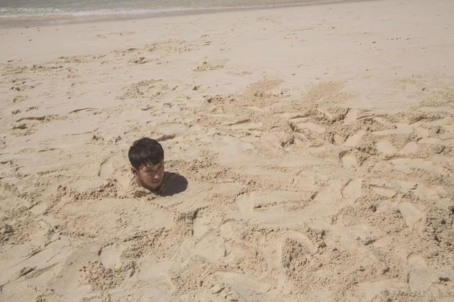 砂浜に埋まり自身の影で方角を確認する男性の写真