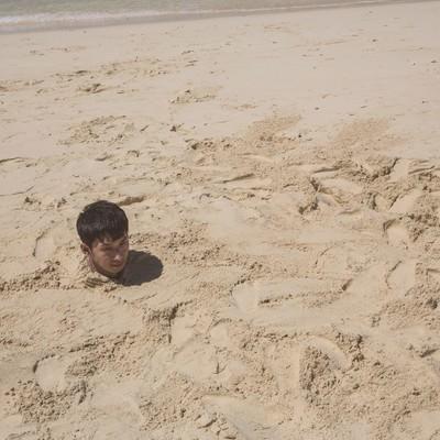 「砂浜に埋まり自身の影で方角を確認する男性」の写真素材