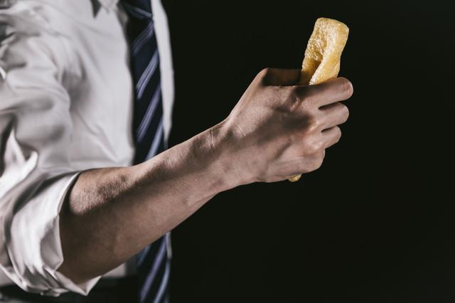 油揚げを握りしめる男性の腕の写真