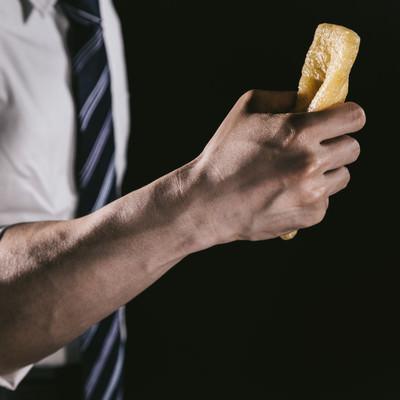 「油揚げを握りしめる男性の腕」の写真素材