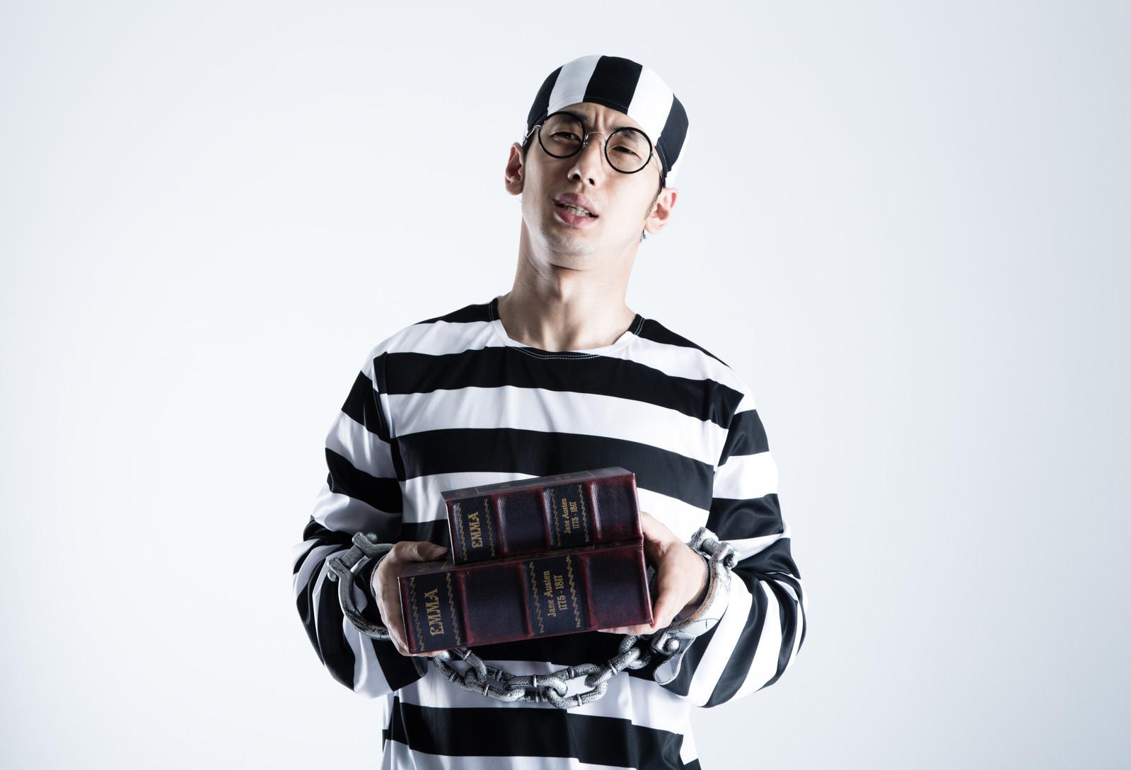 「同じ本のハードカバーと文庫本サイズを購入するうっかり囚人さん」の写真[モデル:大川竜弥]