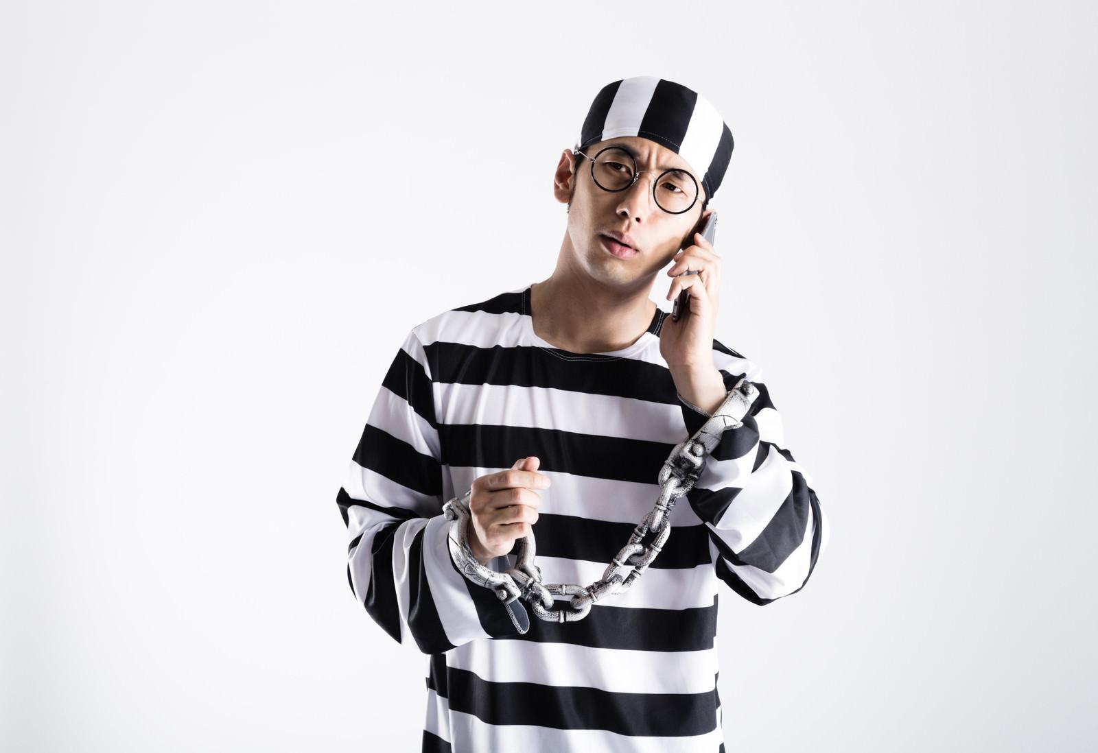 「鍵の110番に電話をする囚人」の写真[モデル:大川竜弥]