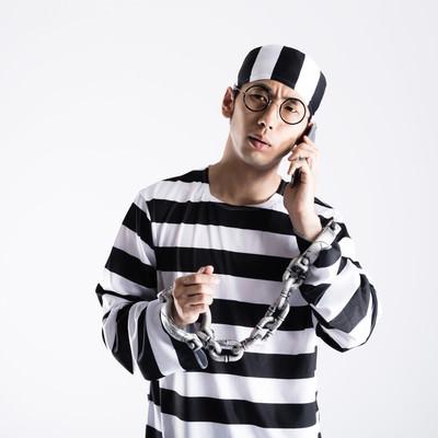 「鍵の110番に電話をする囚人」の写真素材