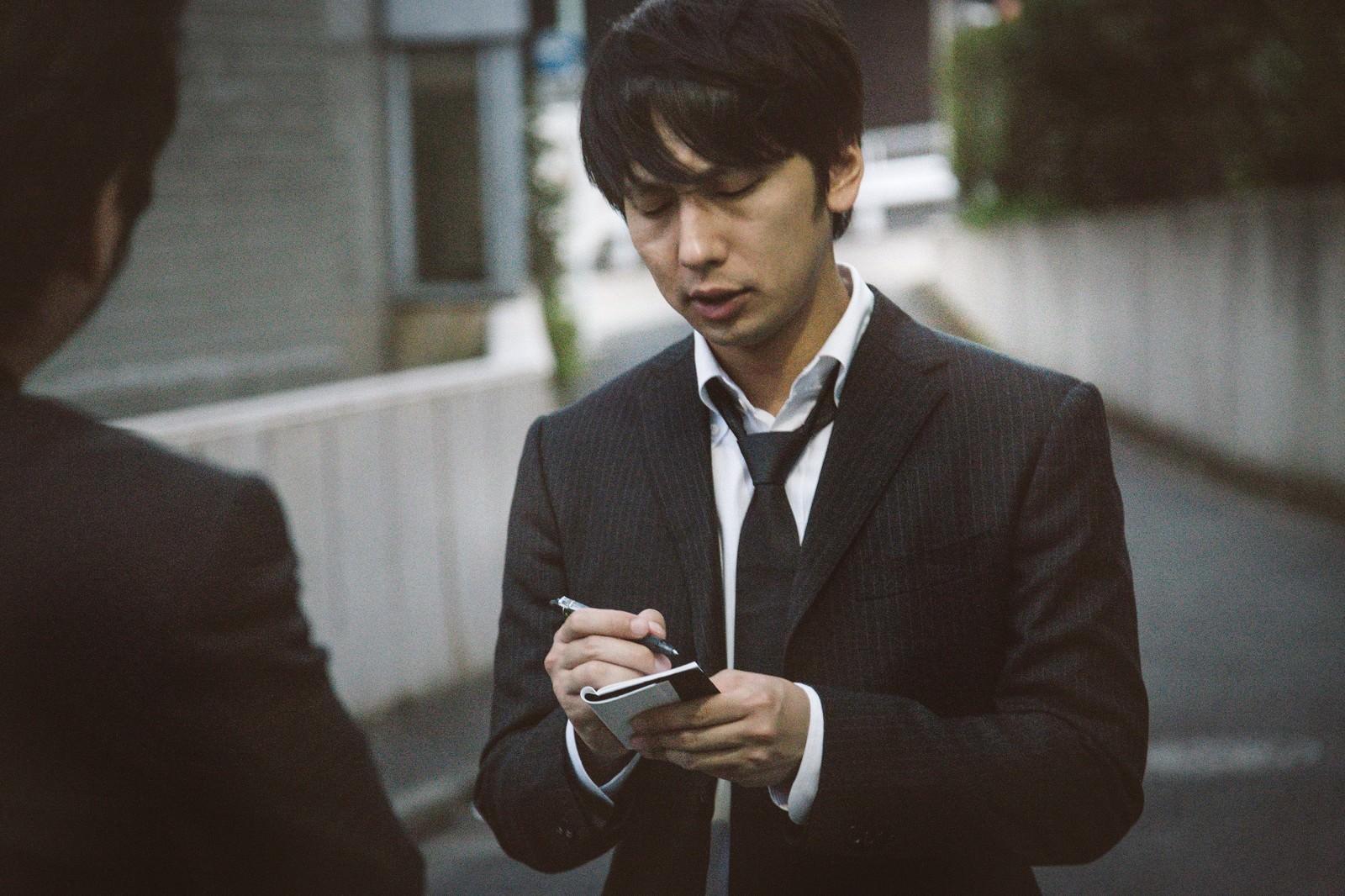 「犯行現場付近で聞き込み取材をする若手記者」の写真[モデル:大川竜弥]