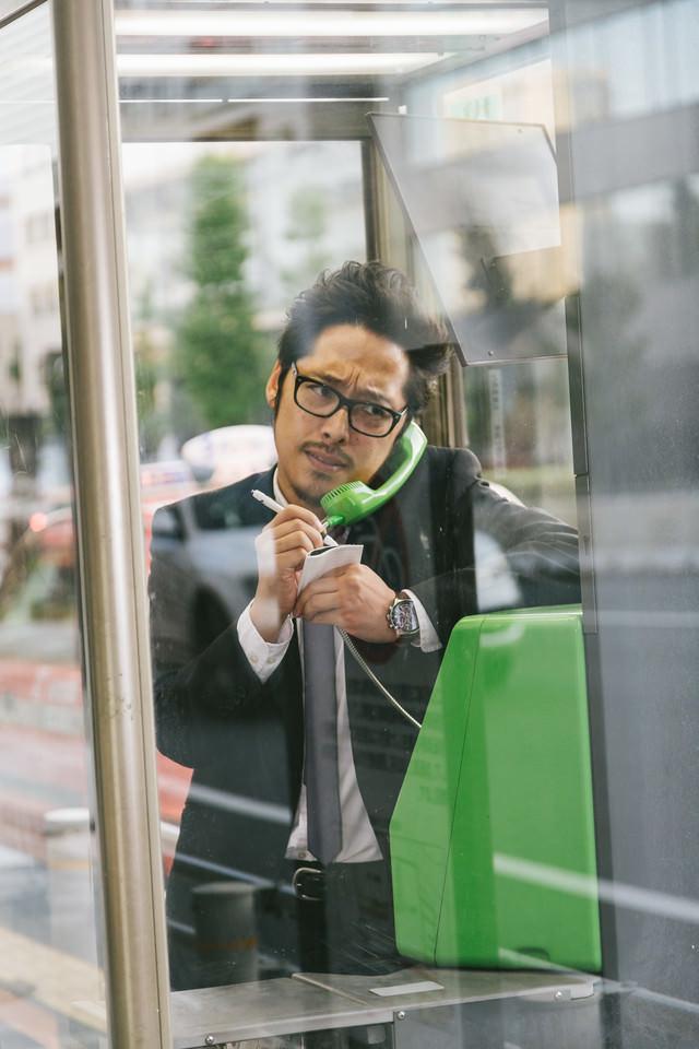 スマホの充電が切れ仕方なく公衆電話を利用する男性の写真
