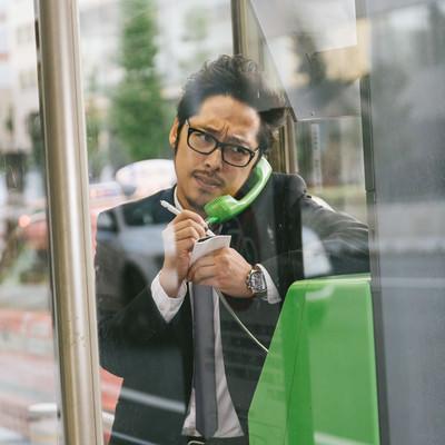 「スマホの充電が切れ仕方なく公衆電話を利用する男性」の写真素材
