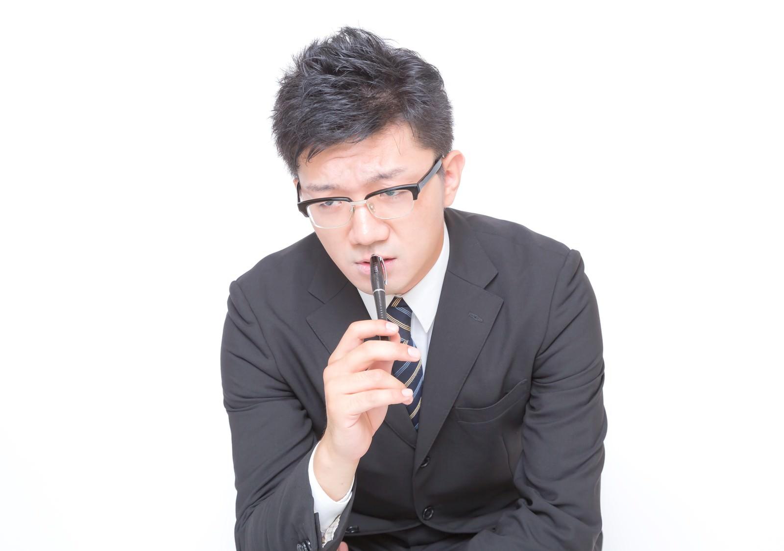 「鬼の形相で睨む(チェックする)ビジネスマン」の写真[モデル:OZPA]