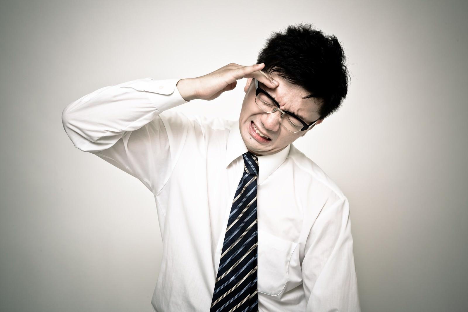 「頭が割れるように痛い会社員の男性」の写真[モデル:OZPA]