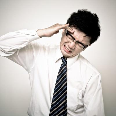 「頭が割れるように痛い会社員の男性」の写真素材
