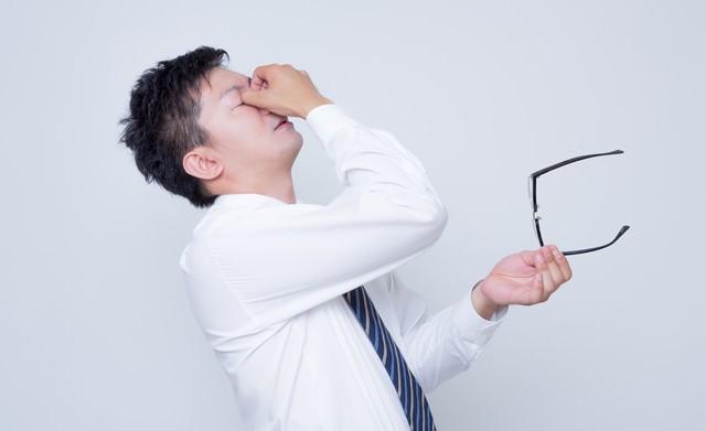 眼球疲労で目をおさえるビジネスマンの写真