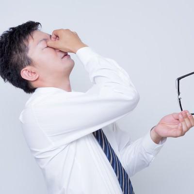 「眼球疲労で目をおさえるビジネスマン」の写真素材