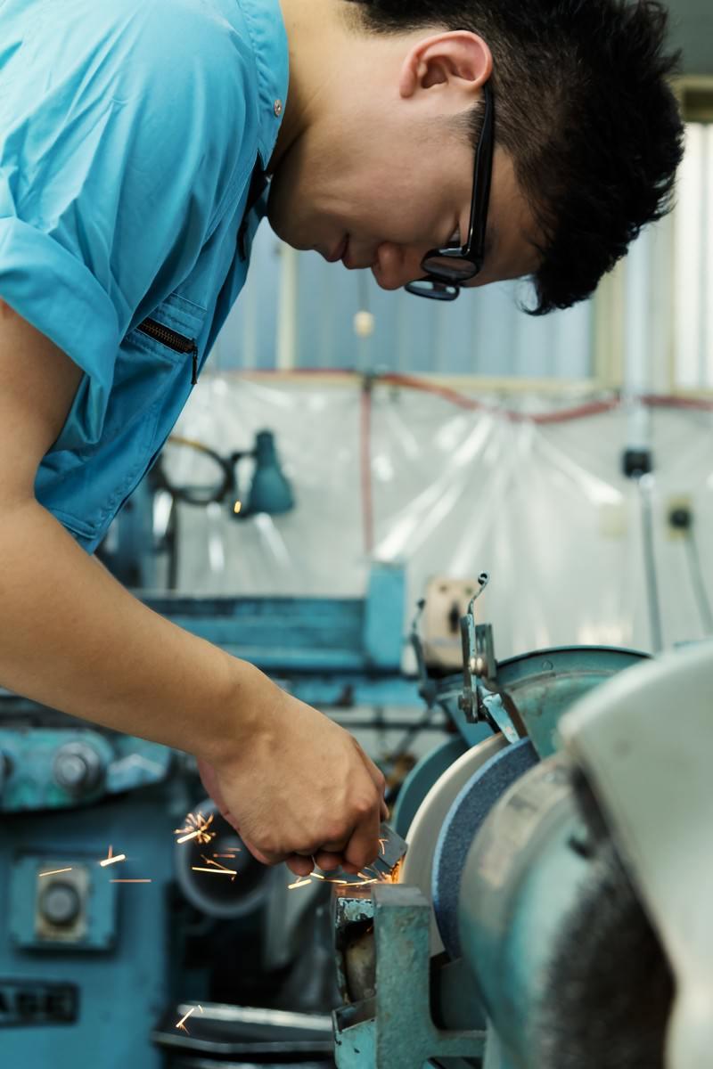 「グラインダーを使って火花を散らす作業中の男性」の写真[モデル:OZPA]
