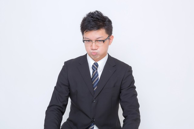 頬をふくらませるビジネスマンの写真