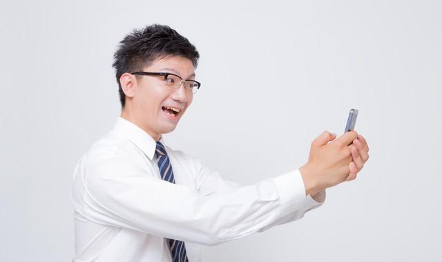 スマートフォンで自撮りするビジネスマンの写真