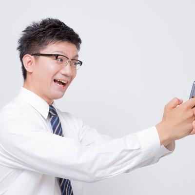 「スマートフォンで自撮りするビジネスマン」の写真素材