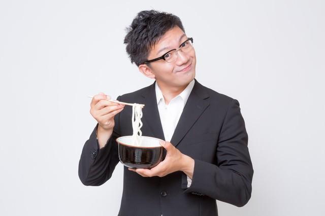 不味そうな素うどんをすくう素うどん面(ヅラ)のビジネスマンの写真