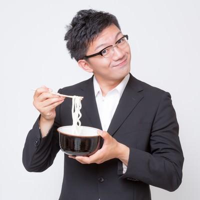 「不味そうな素うどんをすくう素うどん面(ヅラ)のビジネスマン」の写真素材
