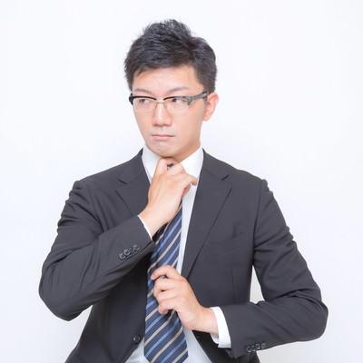 「ネクタイを締め直す眼鏡をかけたビジネスマン」の写真素材