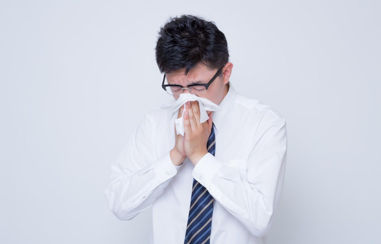 「花粉症で鼻をかむ男性」の写真[モデル:OZPA]