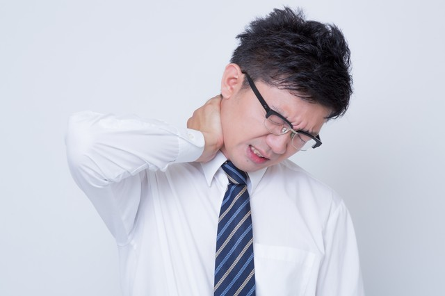 首を寝違えたビジネスマンの写真