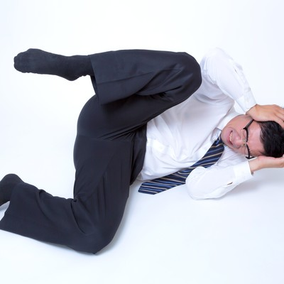 「頭を抱えてジタバタする男性」の写真素材